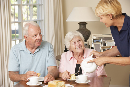 assisting: Senior Couple Enjoying Afternoon Tea Together At Home With Home Help Stock Photo