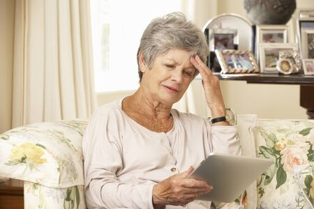 silver surfer: Frustrated Retired Senior Woman Sitting On Sofa At Home Using Digital Tablet Stock Photo