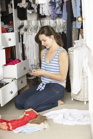 untidy text: Teenage Girl On Mobile Phone Surrounded By Clothes In Wardrobe