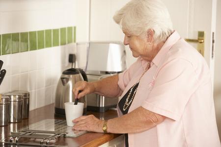 kettles: Retirado de la mujer mayor en la cocina haciendo Bebida caliente