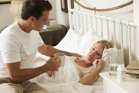 chory: Mąż Bringing chorą żonę gorący napój w łóżku w domu