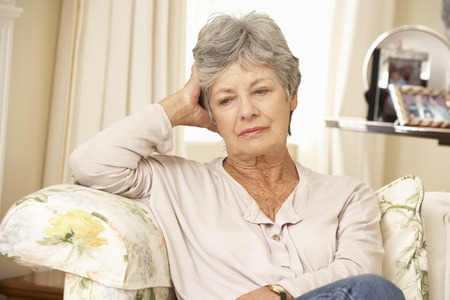 Unhappy Retired Senior Woman Sitting On Sofa At Home Standard-Bild