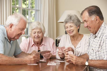Groep hogere koppels genieten spelletje kaarten thuis Stockfoto
