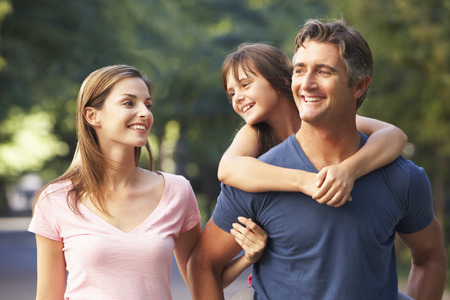 family in park: Dad Giving Daughter Piggyback On Family Walk Through Summer Park Stock Photo