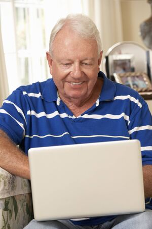 silver surfer: Retired Senior Man Sitting On Sofa At Home Using Laptop
