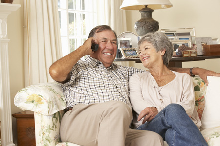 Retired Senior Couple Sitting On Sofa Talking On Phone At Home Together Stock Photo