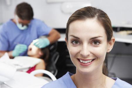 dental nurse: Portrait Of Dental Nurse With Dentist Examining Patient In Background