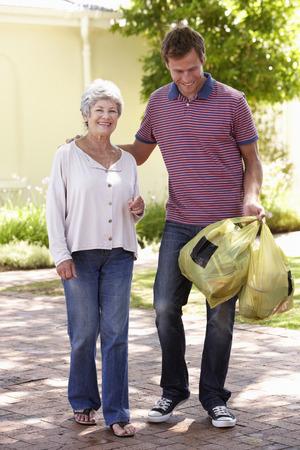 señora mayor: Hombre ayudar a la mujer mayor con Compras