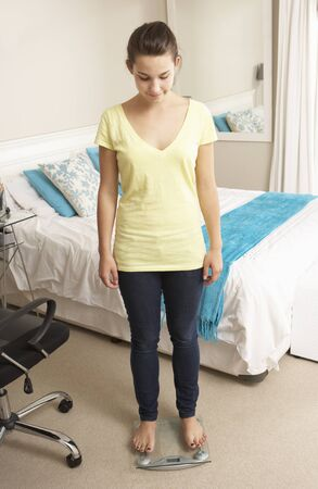 body concern: Teenage Girl Standing On Scales In Bedroom