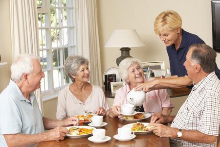 personas comiendo: Grupo de parejas mayores que disfrutan de la comida junto en la atención domiciliaria Con Inicio Ayuda Foto de archivo