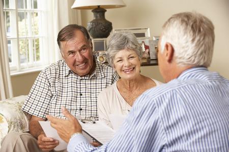 金融アドバイザーに話をソファーの上に座って退職シニア カップル