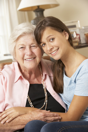 looking after: Teenage Granddaughter Visiting Grandmother At Home Stock Photo