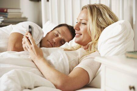 pareja durmiendo: Mujer que usa el tel�fono m�vil en la cama Marido Mientras Duermen