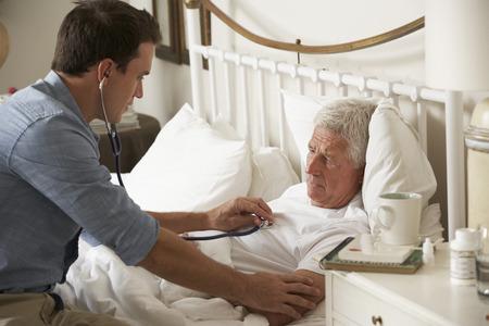 Arts Onderzoekende Senior Mannelijke Patiënt In Bed Thuis Stockfoto