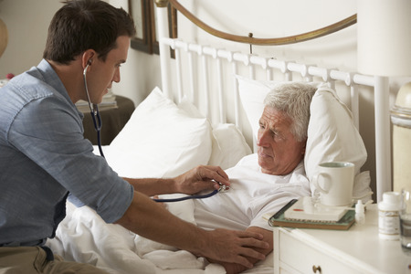 palliative: Doctor Examining Senior Male Patient In Bed At Home