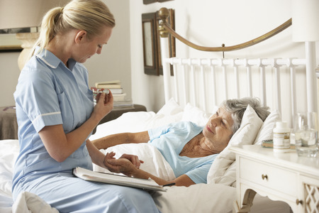 healthcare visitor: Nurse Taking Pulse Of Senior Patient Patient In Bed At Home Stock Photo