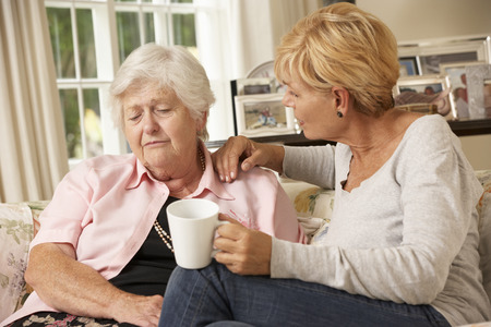 senior adult: Adult Daughter Visiting Unhappy Senior Mother Sitting On Sofa At Home