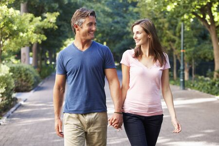 parejas caminando: Pares románticos que recorren a través de parque de verano