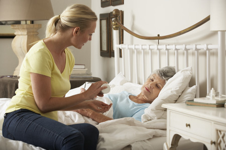 palliative: Adult Daughter Giving Senior Female Parent Medication In Bed At Home