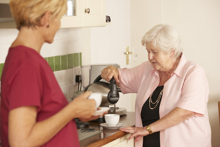 sheltered: Home Help Sharing Cup Of Tea With Senior Woman In Kitchen