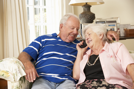 couple talking: Retired Senior Couple Sitting On Sofa Talking On Phone At Home Together Stock Photo