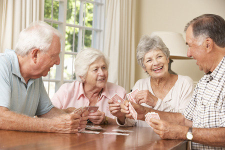 table: Group Of Senior Couples Enjoying Game Of Cards At Home