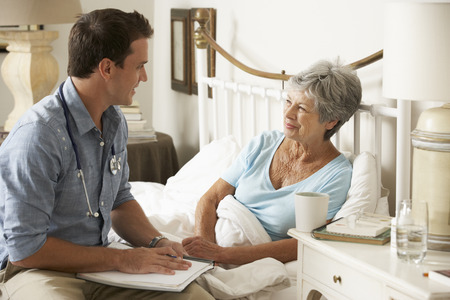 Doctor Talking With Senior Female Patient In Bed At Home Stock Photo