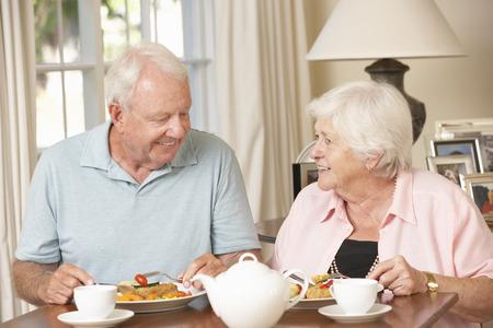 老夫婦の家で一緒に食事を楽しんで 写真素材