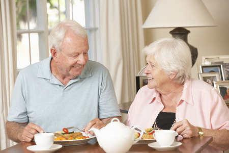 senior eating: Senior Couple Enjoying Meal Together At Home