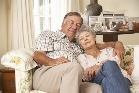 pareja durmiendo: Pares mayores jubilados que dormita en el sofá en el país junto