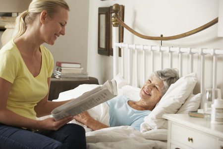 palliative: Adult Daughter Reading Newspaper To Senior Female Parent In Bed At Home Stock Photo