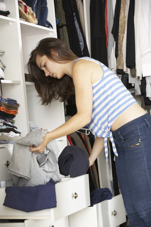 messy clothes: Teenage Girl Choosing Clothes From Wardrobe In Bedroom