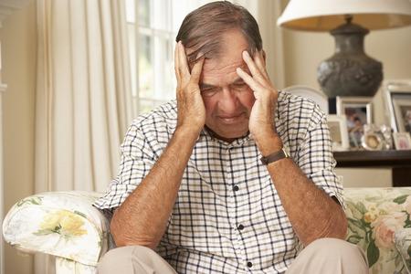 persona de la tercera edad: Descontento Retirado hombre mayor sentado en el sofá en casa