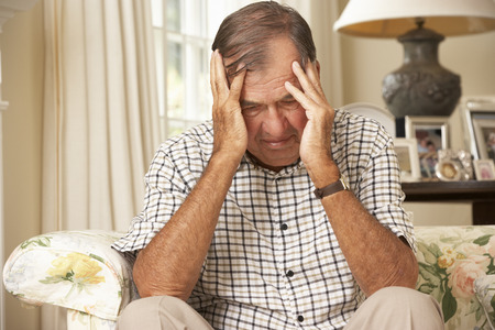 man couch: Unhappy Retired Senior Man Sitting On Sofa At Home