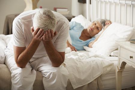 妻が眠る間心配している年配の男性がベッドに座っています。 写真素材