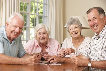 シニア グループ カップル カードのゲームを家庭で楽しむ