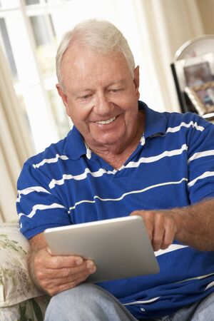 silver surfer: Retired Senior Man Sitting On Sofa At Home Using Tablet Computer