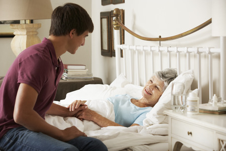 Teenage Grandson Visiting Grandmother In Bed At Home