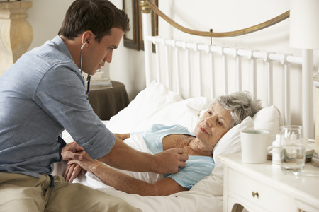 palliative: Doctor Examining Senior Female Patient In Bed At Home Stock Photo