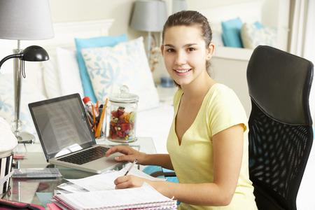 10 代の少女の寝室の机で勉強して
