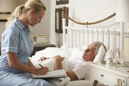 visit: Nurse Visiting Senior Male Patient In Bed At Home Stock Photo