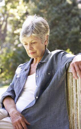 senior depression: Unhappy Senior Woman Sitting On Park Bench