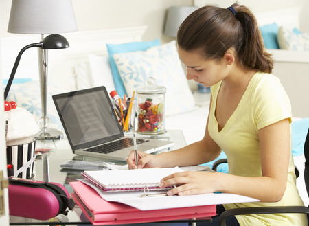 Teenage Girl Studying At Desk In Bedroom Reklamní fotografie