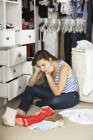 messy clothes: Unhappy Teenage Girl Unable To Find Suitable Outfit In Wardrobe