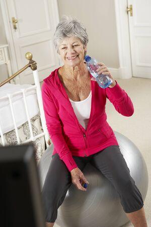 personas saludables: Mujer mayor que ejercita mientras que ve la aptitud de DVD en la televisión