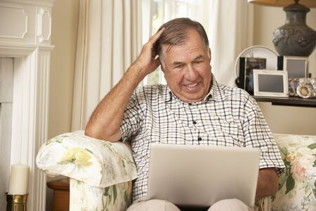 Frustrated Retired Senior Man Sitting On Sofa At Home Using Laptop Stock Photo