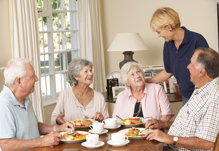 mature people: Group Of Senior Couples Enjoying Meal Together In Care Home With Home Help