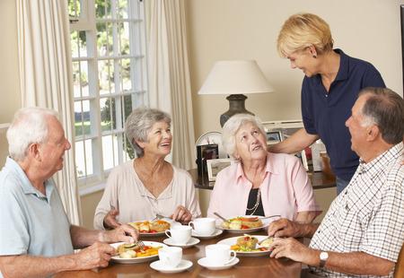 lunch: Grupo de parejas mayores que disfrutan de la comida junto en la atenci�n domiciliaria Con Inicio Ayuda Foto de archivo