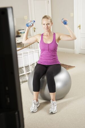 keeping room: Woman Exercising Whilst Watching Fitness DVD On Television