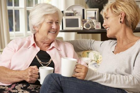 hija: La hija adulta Visitar senior madre sentada en el sofá en casa